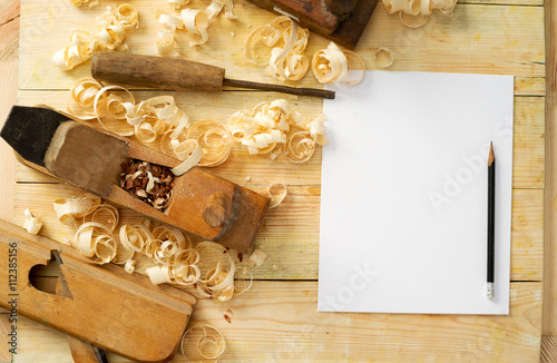 Fotografie, Obraz  White sheet on wooden table for carpenter tools with sawdust.