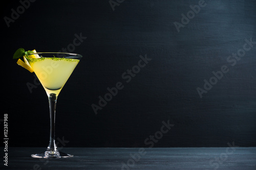 Fotografia Yellow martini cocktail with lemon and mint on the rustic wooden background