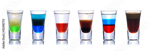 Vászonkép Set of colorful alcoholic cocktails in shot glasses isolated on white with reflection