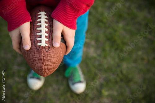 Plakat Odgórny widok na rękach małego dziecka chłopiec mienia futbol na stadium na słonecznym dniu. Dziecko gotowe do rzucenia piłki nożnej. Pojęcie sportu. Zajęcia sportowe dla dzieci na zewnątrz.