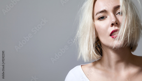 Fotografía Close up face woman with red lips and sensual look on a grey background isolated