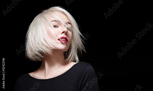 Cuadros en Lienzo Fashionable woman with red lipstick and short hair on black background