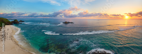 Panoramic view of tropical beach with surfers at sunset. - 112429921