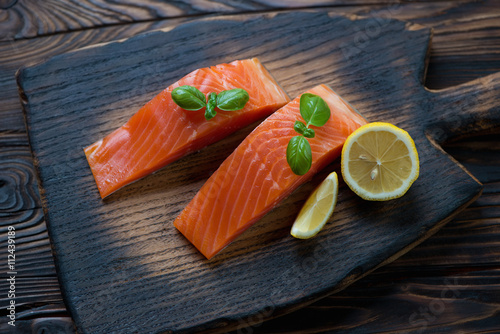 Foto  Rustic wooden chopping board with sliced smoked trout fillet