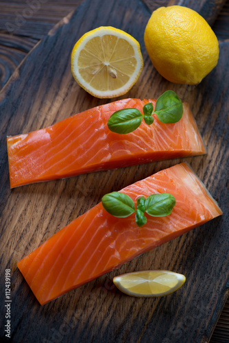 Fotografie, Tablou  Close-up of smoked trout fillet with lemon and basil, above view