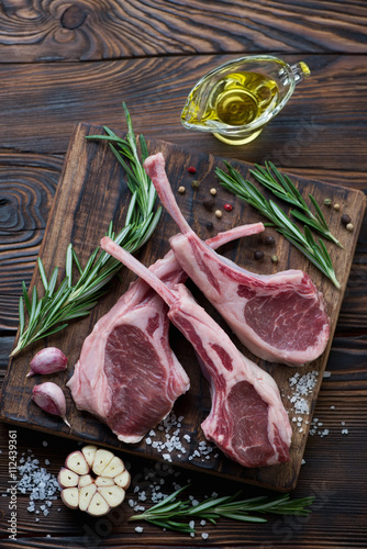 Photo  Fresh uncooked lamb chops with condiments, rustic wooden setting