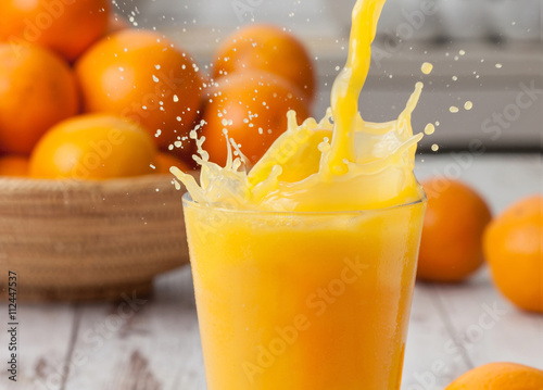 Foto auf Gartenposter Saft Orange juice pouring splash