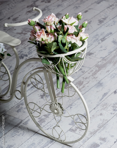 Foto op Plexiglas Fiets Garden white bicycle with a a basket of flowers roses