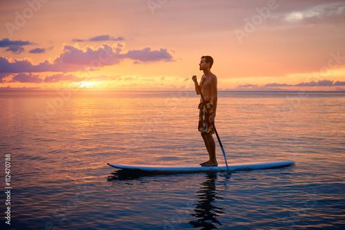Plakat Sylwetka mężczyzna paddleboarding przy zmierzchem