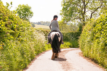 Young girl riding down the Shropshire lanes while looking behind her