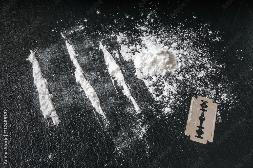 Photo  Cocaine white powder in lines and razor. Narcotics concept.
