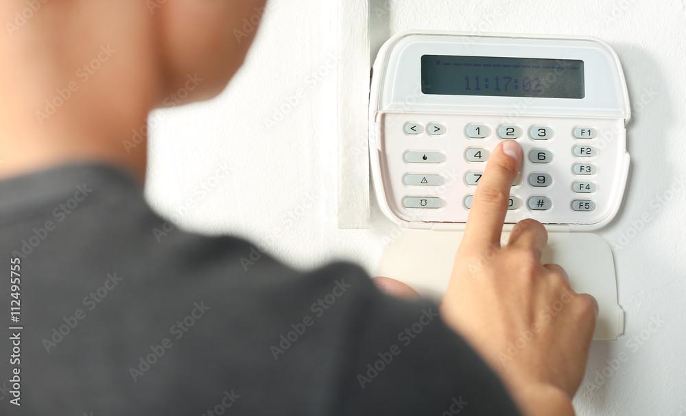 Fototapeta Man pressing the code on a house alarm