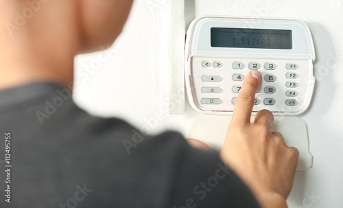 Photo Man pressing the code on a house alarm