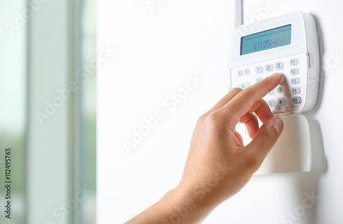 Male hand pressing the code on a house alarm Wallpaper Mural