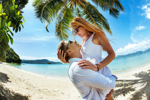 Young Amorous Couple Hugging On A Tropical Beach Under The Palm