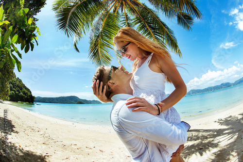 Fotografia  Young amorous couple hugging on a tropical beach under the palm