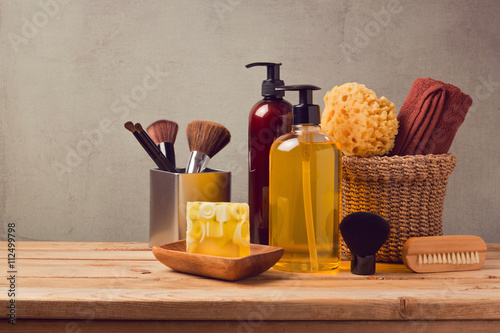 Fotografía  Body care products on wooden table over gray background