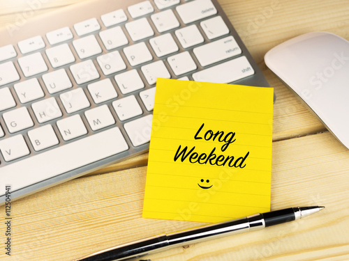 Fényképezés  Long weekend on sticky note on work desk