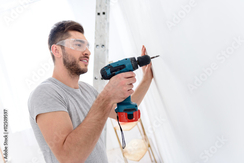 Young guy drilling white wall