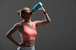 Attractive young woman enjoying drink after exercising