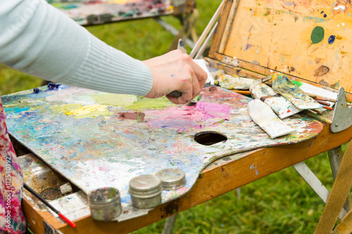Cuadros en Lienzo Female artist's hand mixing colors with a paletteknife in a park