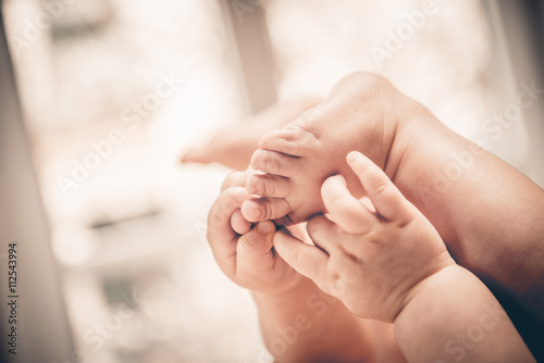 Photo  Baby holds his small hands their feet