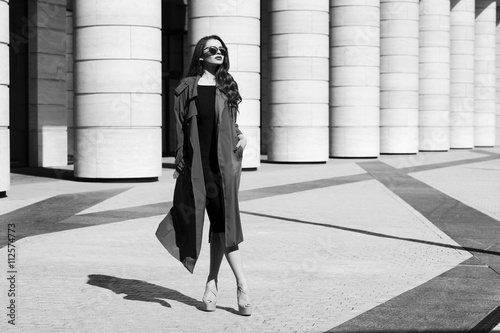 Fényképezés  Fashion vogue style dynamic portrait of young beautiful pretty woman posing at city street in black dress, gray coat and sunglasses