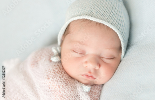 beautiful sleeping newborn baby in hat and wrapped close-up