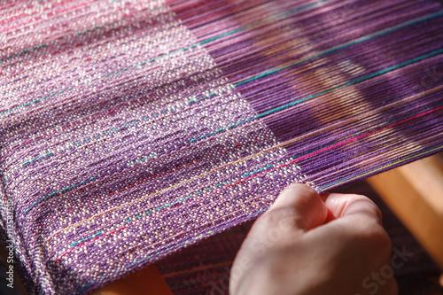 Slika na platnu Hands of the woman weaving on a loom