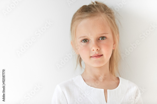 Valokuva  Pretty little girl with Caucasian traits looking peacefully and standing still like obedient child