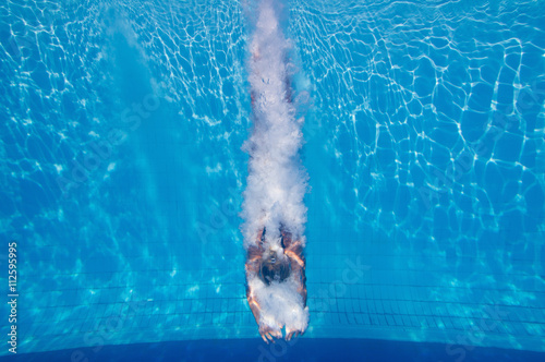 Fotografía Diving into the swimming pool, leaving bubble trail behind