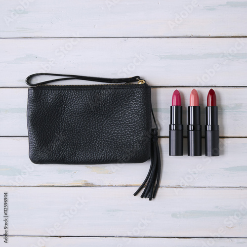 Valokuva A black leather purse and lipsticks on a wooden background