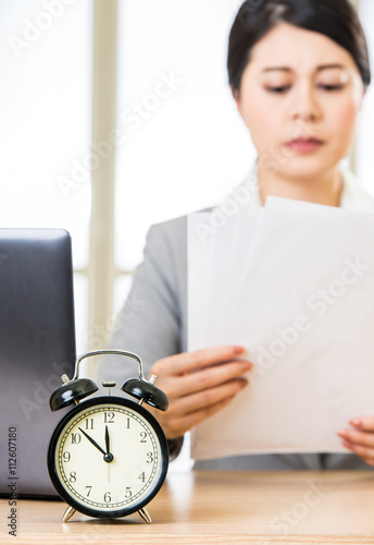 Fototapeta Businesswoman with papers over table with alarm clock laptop obraz na płótnie