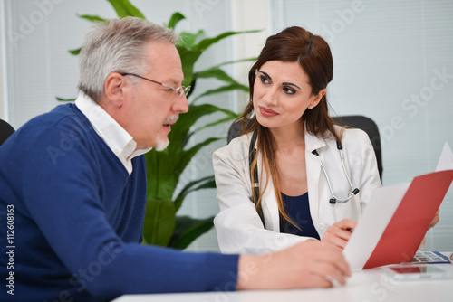 Doctor speaking to her patient while showing some documents Poster