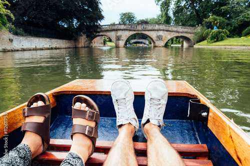 Man and woman feet on a boat punting in the river in  Cambridge Fotobehang