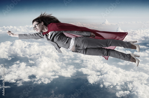 Superwoman flying above the skies Wallpaper Mural