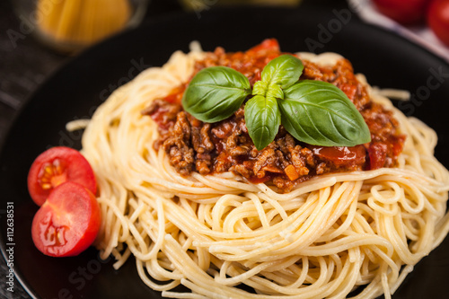 фотография  Spaghetti bolognese on dark background