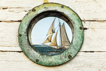 Fototapeta Marynistyczny Old porthole window looks out at an old sailing ship. Vintage color