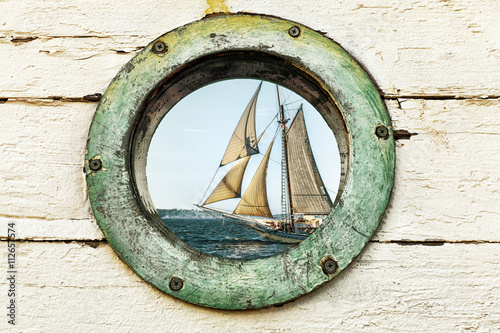 Photo Stands Ship Old porthole window looks out at an old sailing ship. Vintage color