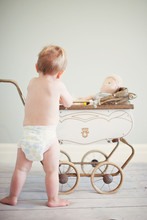 Baby Boy Wearing Nappy Playing With Pram