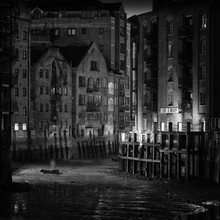 B&W Photo Of A Dickensian Wharf With Victorian Warehouses At Night