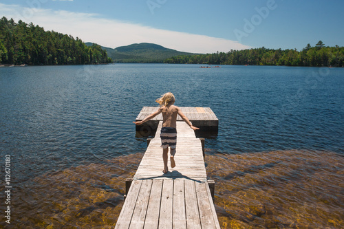 Young boy walking along jetty on lake, rear view Poster