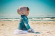 a little girl sitting on the beach