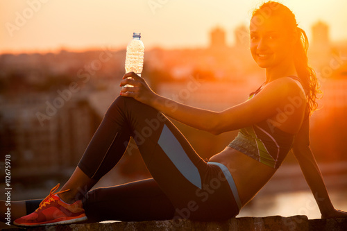 Keuken foto achterwand Ontspanning silhouette of Young sportswoman with a bottle of water resting,