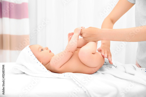 Obraz na plátně  Mother hands applying cream on little baby body in room