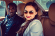 Smiling female in sunglasses in a car with black man.