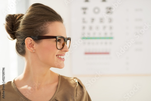 Fotografía  Mujer joven feliz llevando gafas delante de la tabla de Snellen