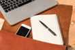 Blank business laptop, mouse, pen, note and glasses on wooden table