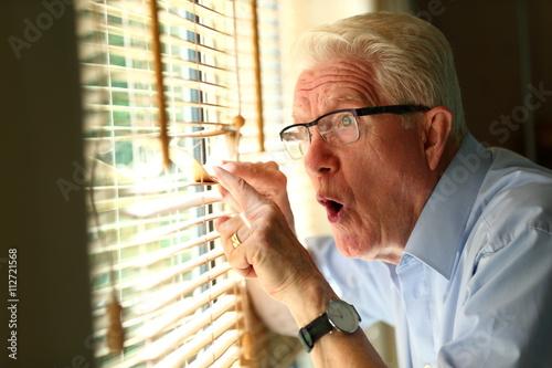 Fotografía  curiosity/ curious senior man looking through the blinds of his window