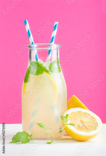 Fotografía  Bottle of homemade lemonade with mint, ice, lemons, paper straws and bright purp